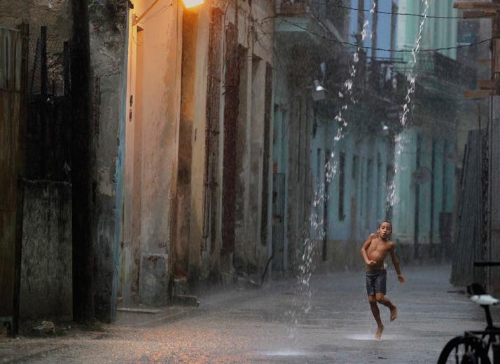 A boy dances in the rain during a heavy tropical shower in a street of Havana