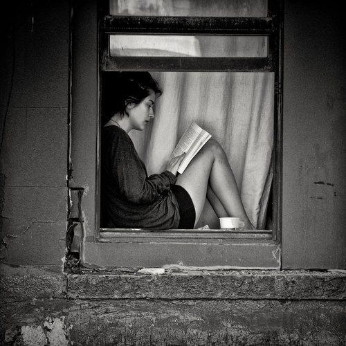 mujer ventana leyendo