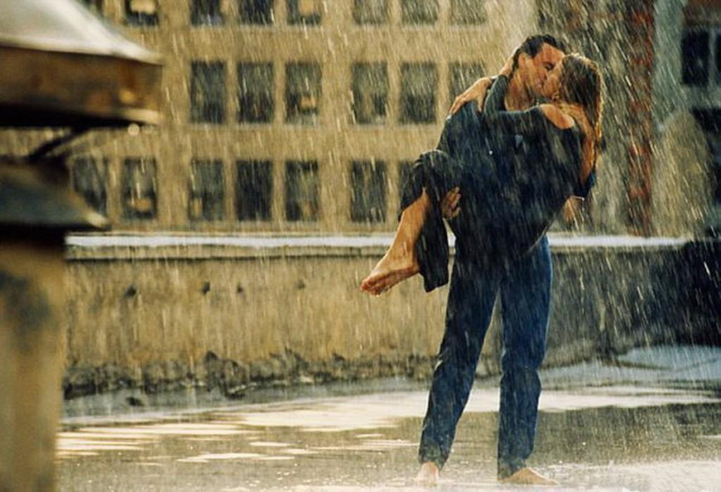 persona intensa beso bajo la lluvia