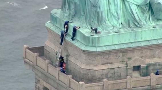 mujer escala estatua de la libertad en protesta por la politica migratoria 1