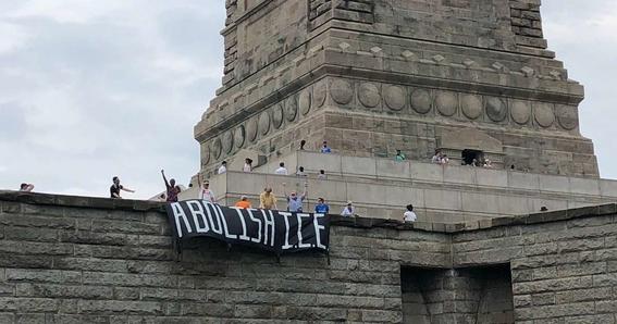 mujer escala estatua de la libertad en protesta por la politica migratoria 2