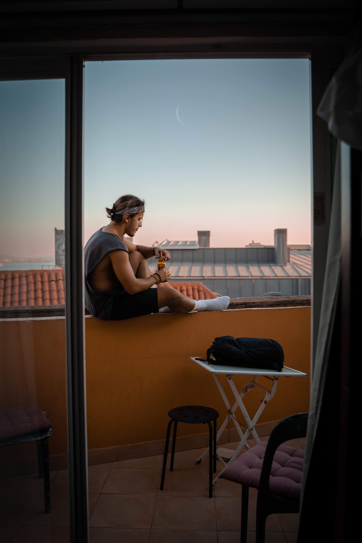 man sitting on balcony drinking beer