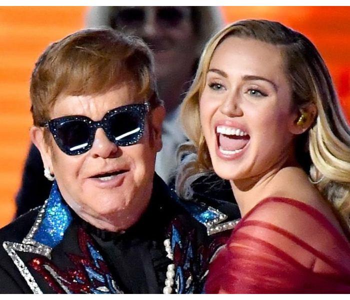 Miley Cyrus hugging Elton John