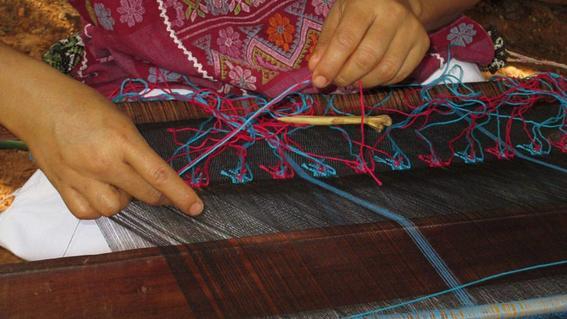 mujer amuzga tejiendo en telar de cintura