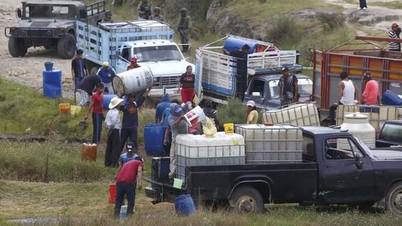 personas robando combustible de un ducto perforado