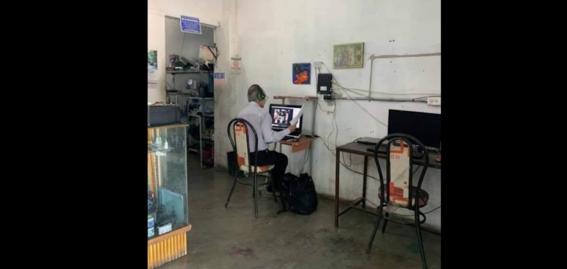 profesor da clases en linea desde un cafe internet