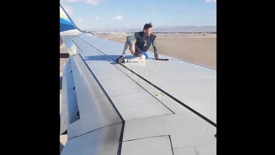 hombre se subio al ala de un avion a punto de despegar