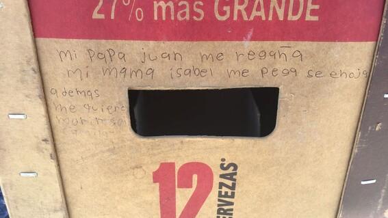 nina pide auxilio escribiendo mensaje en carton de cervezas